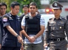 Thai police officers escort Iranian bomb suspect Mohammad Kharzei (C) during an investigation at his rented house in Bangkok on February 20, 2012.  Police in Thailand said on February 17 they were hunting for a fifth Iranian suspected in a failed bomb plot in Bangkok that has sent tensions between Israel and Iran soaring.  TOPSHOTS    AFP PHOTO / PORNCHAI KITTIWONGSAKUL (Photo credit should read PORNCHAI KITTIWONGSAKUL/AFP/Getty Images)