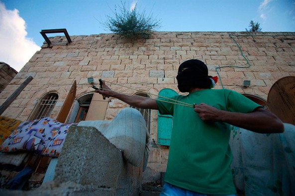A Palestinian protester aims a slingshot towards Israeli soldiers