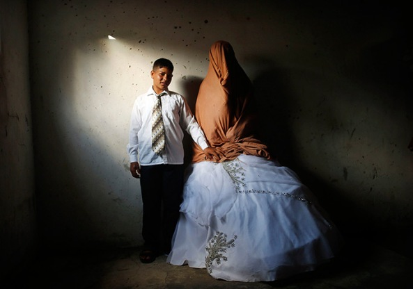 Palestinian groom Ahmed Soboh, 15, and his bride Tala, 14, stand inside Tal
