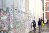 Visitors to the festival inscribe their messages on the replica wall at St. James Church, London.