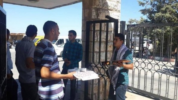 University students in Birzeit University distribute sweets in celebration of the kidnapping of the three Israeli teenagers.